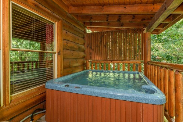 Hot tub on a covered deck at Little Chateau, a 1 bedroom cabin rental located in Pigeon Forge