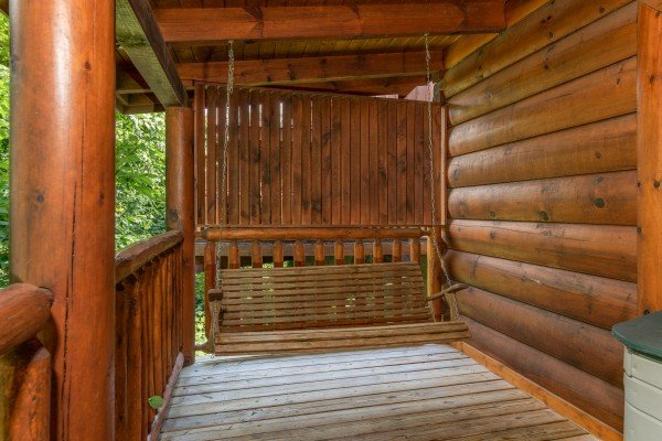 Porch swing on a covered deck at Little Chateau, a 1 bedroom cabin rental located in Pigeon Forge