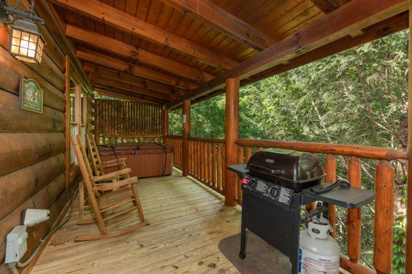 Grill and rocking chairs on a covered deck at Little Chateau, a 1 bedroom cabin rental located in Pigeon Forge