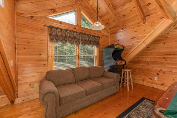 Sleeper sofa in the game room at Little Chateau, a 1 bedroom cabin rental located in Pigeon Forge