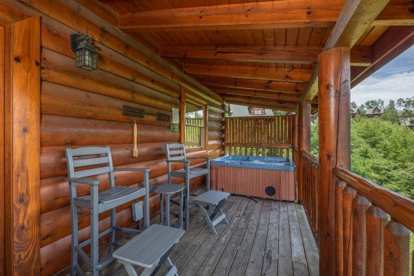 High chairs and hot tub on a deck at Azalea Point, a 2 bedroom cabin rental located in Pigeon Forge