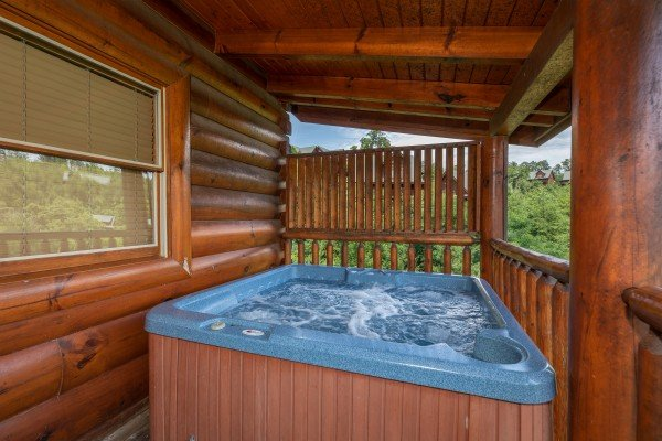 Hot tub on a covered deck at Azalea Point, a 2 bedroom cabin rental located in Pigeon Forge