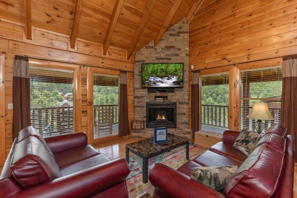 Living room with fireplace, TV, sofa, and love seat at Azalea Point, a 2 bedroom cabin rental located in Pigeon Forge