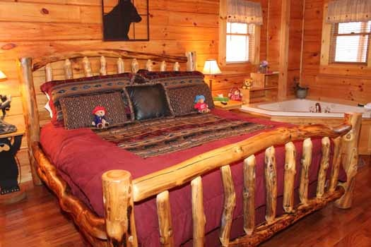 king sized custom log framed bed next to jacuzzi tub in the bedroom at bear bottom a 1 bedroom cabin rental located in gatlinburg