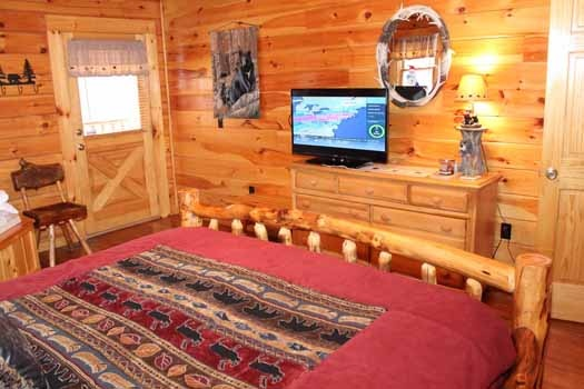 chest of drawers with tv on top at the foot of the bed at bear bottom a 1 bedroom cabin rental located in gatlinburg