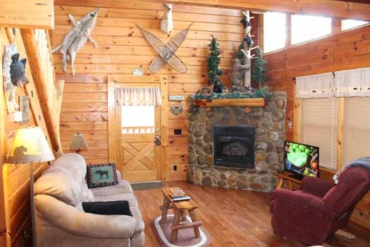 a stone fireplace in the corner of the living room with a tv sitting next to it at bear bottom a 1 bedroom cabin rental located in gatlinburg