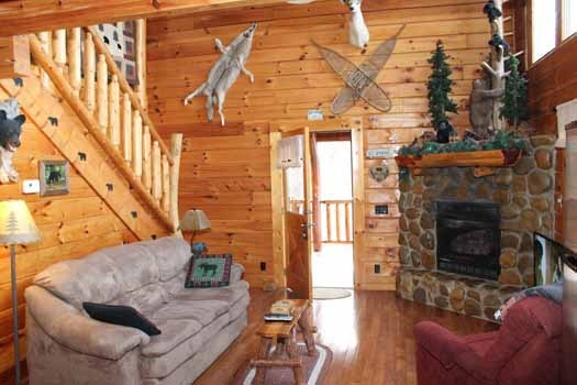 living room view of staircase and front door at bear bottom a 1 bedroom cabin rental located in gatlinburg