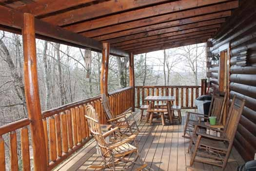 four rocking chairs along with a picnic table on the deck at bear bottom a 1 bedroom cabin rental located in gatlinburg