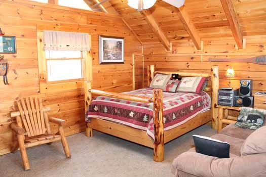 queen sized log framed bed in second floor bedroom at bear bottom a 1 bedroom cabin rental located in gatlinburg