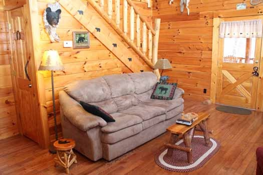 sofa bed in the living room at bear bottom a 1 bedroom cabin rental located in gatlinburg