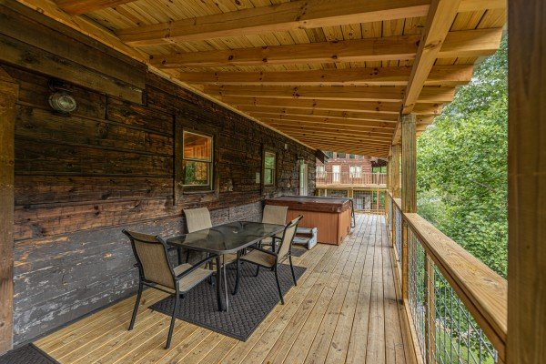 Hot tub and dining table for 4 at amazing journey a 5 bedroom cabin rental located in pigeon forge