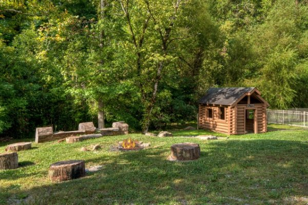 fire pit with log seating at alpine mountain village at amazing journey a 5 bedroom cabin rental located in pigeon forge