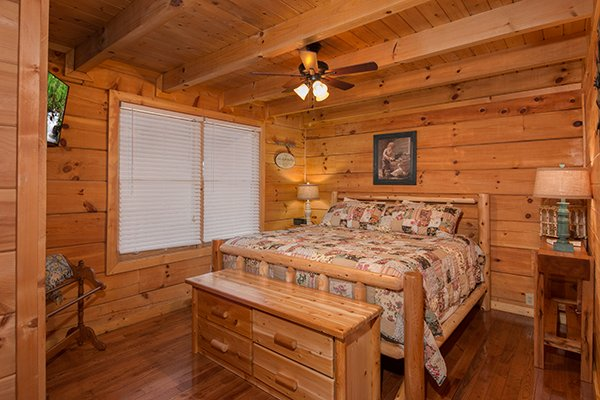 king sized log bed with dresser at amazing journey a 5 bedroom cabin rental located in pigeon forge