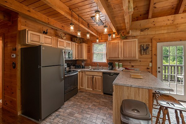 kitchen with stainless steel appliances and bar seating at amazing journey a 5 bedroom cabin rental located in pigeon forge