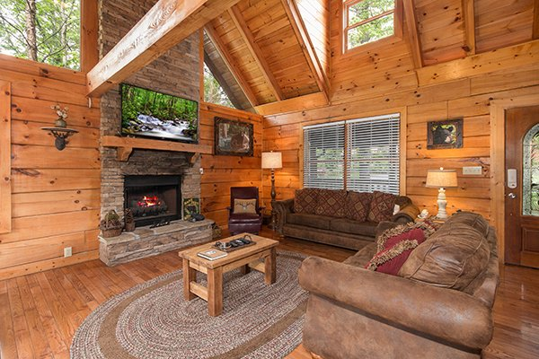 vaulted living room with stone fireplace and television at amazing journey a 5 bedroom cabin rental located in pigeon forge
