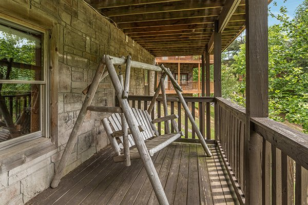 log porch swing on a covered deck at amazing journey a 5 bedroom cabin rental located in pigeon forge