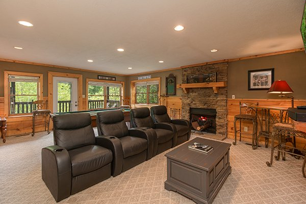 four recliners near a fireplace in the theater room at amazing journey a 5 bedroom cabin rental located in pigeon forge