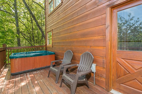 Hot tub and two Adirondack chairs on a deck at Patriot Inn, a 1 bedroom Gatlinburg cabin rental