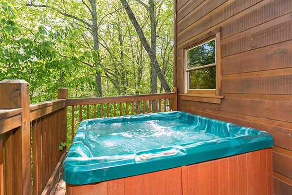 Hot tub on a deck surrounded by woods at Patriot Inn, a 1 bedroom Gatlinburg cabin rental