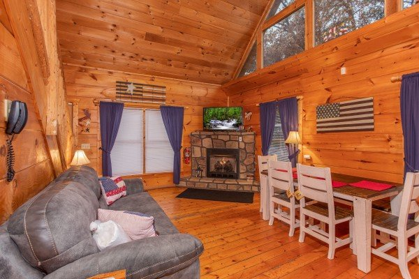 Living room with fireplace, TV, and dining space at Patriot Inn, a 1 bedroom Gatlinburg cabin rental