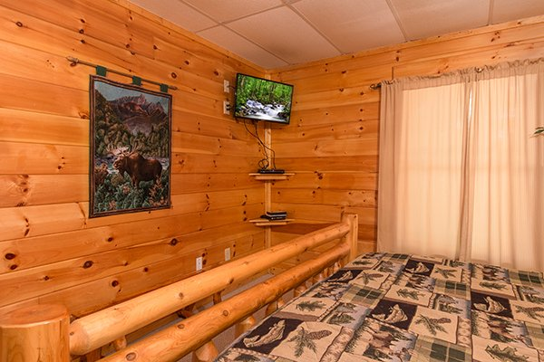 log bed and wall mounted television at animal kingdom a 4 bedroom cabin rental located in gatlinburg