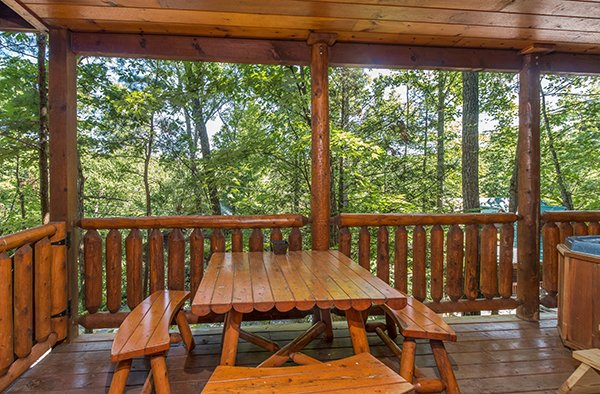 picnic table on a covered deck at animal kingdom a 4 bedroom cabin rental located in gatlinburg