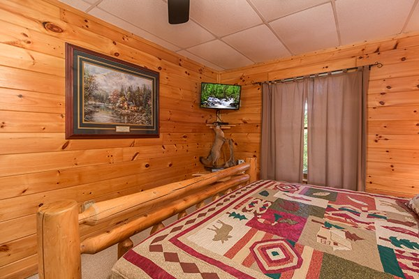 king sized bed and wall mounted television at animal kingdom a 4 bedroom cabin rental located in gatlinburg