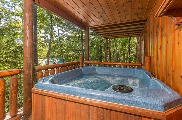 hot tub on the covered deck at animal kingdom a 4 bedroom cabin rental located in gatlinburg