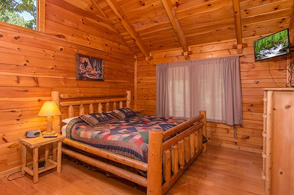 king sized log bed and a wall mounted television at animal kingdom a 4 bedroom cabin rental located in gatlinburg
