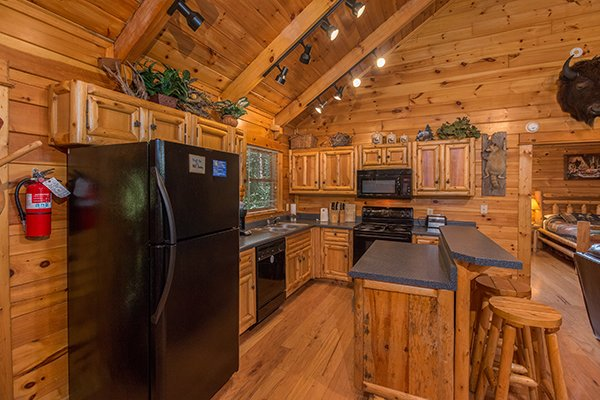 kitchen with black appliances and bar top seating at animal kingdom a 4 bedroom cabin rental located in gatlinburg