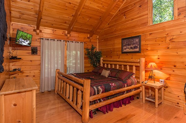 log bed with wall mounted television at animal kingdom a 4 bedroom cabin rental located in gatlinburg
