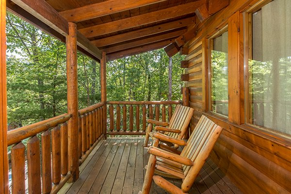 log rocking chairs on a covered deck at animal kingdom a 4 bedroom cabin rental located in gatlinburg