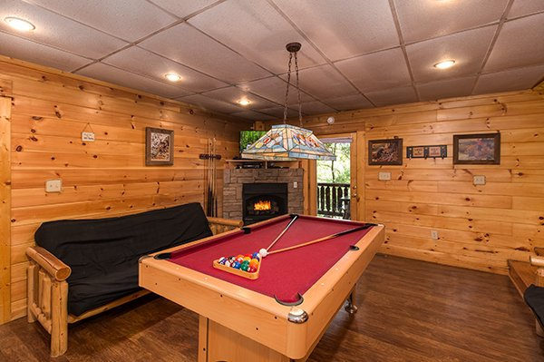 pool table near a futon and fireplace at animal kingdom a 4 bedroom cabin rental located in gatlinburg
