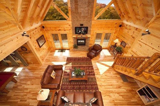 view of the living room and tall stone fireplace from loft at big bear cove a 3 bedroom cabin rental located in gatlinburg