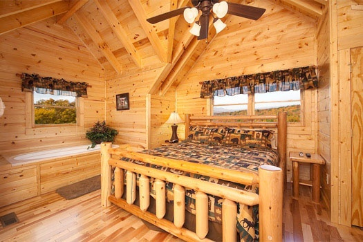king sized custom log bed next to jacuzzi tub at big bear cove a 3 bedroom cabin rental located in gatlinburg