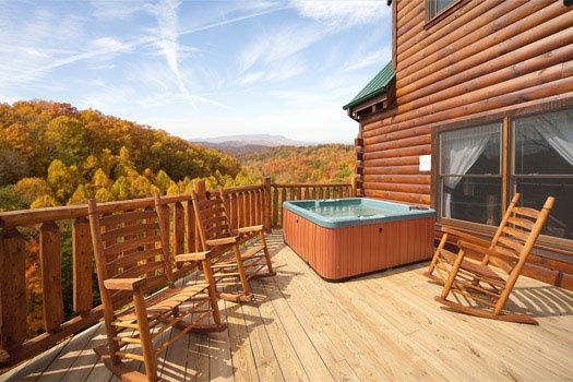 rocking chairs sitting in front of a hot tub on the deck at big bear cove a 3 bedroom cabin rental located in gatlinburg