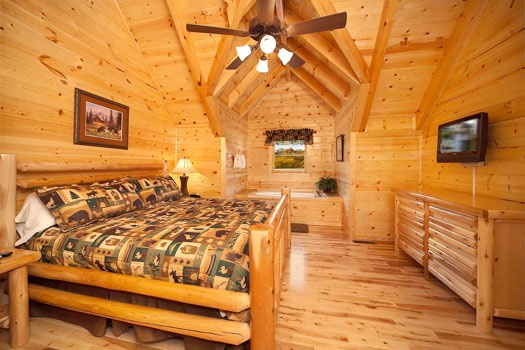 king sized bed with jacuzzi in room at big bear cove a 3 bedroom cabin rental located in gatlinburg