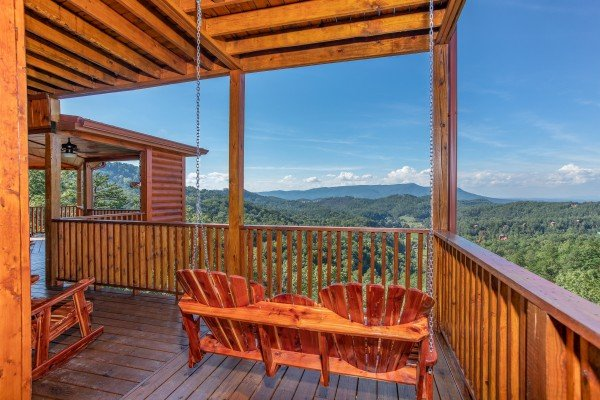 Adirondack style porch swing overlooking the views at Four Seasons Palace, a 5-bedroom cabin rental located in Pigeon Forge