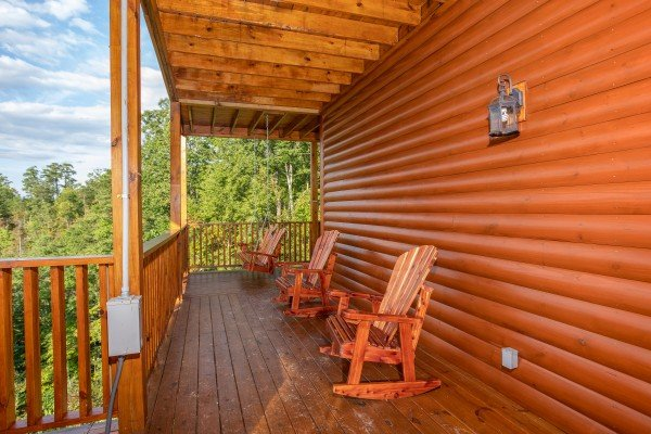 Deck rockers in a row on a covered porch at Four Seasons Palace, a 5-bedroom cabin rental located in Pigeon Forge