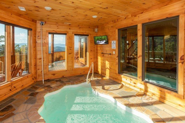 Indoor pool room with a TV at Four Seasons Palace, a 5-bedroom cabin rental located in Pigeon Forge