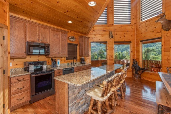 Kitchen with stainless appliances and counter seating for four at Four Seasons Palace, a 5-bedroom cabin rental located in Pigeon Forge
