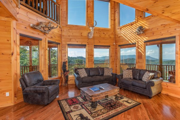 Floor to ceiling windows in a vaulted living room at Four Seasons Palace, a 5-bedroom cabin rental located in Pigeon Forge