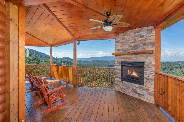 Outdoor fireplace and rocking chairs on the covered deck at Four Seasons Palace, a 5-bedroom cabin rental located in Pigeon Forge