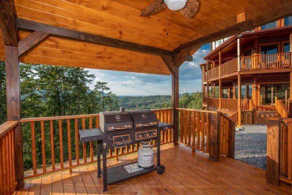 Propane grill on a covered deck at Four Seasons Palace, a 5-bedroom cabin rental located in Pigeon Forge