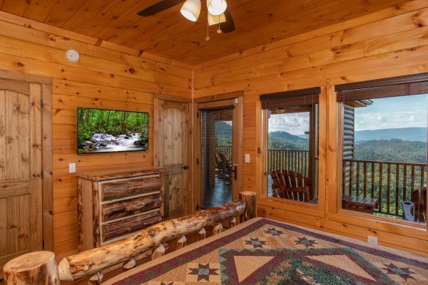 Bedroom with a dresser, TV, deck access, and mountain views at Four Seasons Palace, a 5-bedroom cabin rental located in Pigeon Forge