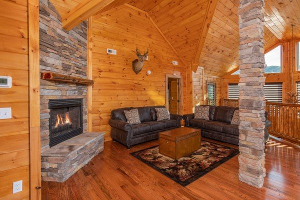 Upper living room with a fireplace and plenty of seating at Four Seasons Palace, a 5-bedroom cabin rental located in Pigeon Forge