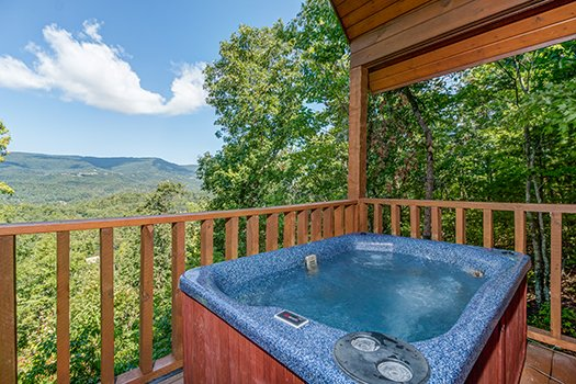 Hot tub on a covered deck with mountain views at Cupid's Crossing, a 1-bedroom cabin rental located in Pigeon Forge