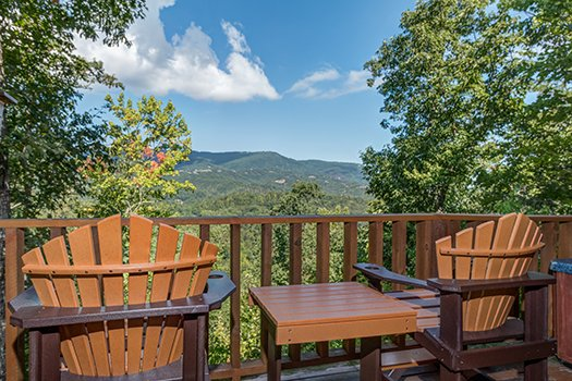 Two deck chairs with a table overlooking the mountains at Cupid's Crossing, a 1-bedroom cabin rental located in Pigeon Forge