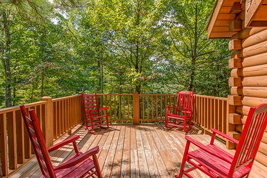 Deck with rocking chairs surrounded by the woods at Cupid's Crossing, a 1-bedroom cabin rental located in Pigeon Forge
