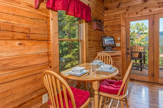 Dining table with seating for three at Cupid's Crossing, a 1-bedroom cabin rental located in Pigeon Forge